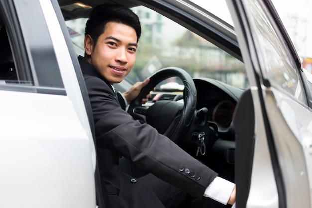 Молодой предприниматель открывает дверь своей машины Premium Фотографии