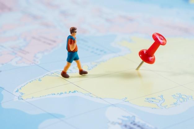 Мини-путешественник с красной кнопкой и концепция путешествия на карте Бесплатные Фотографии
