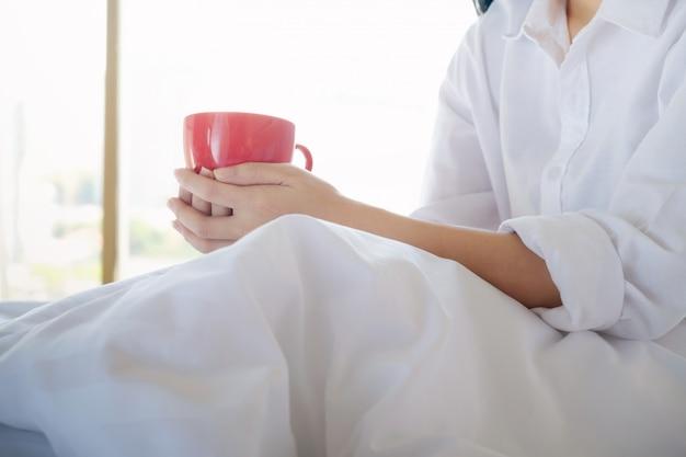 ベッドに座っている彼女のコーヒーを楽しむリラックスした女性。 Premium写真