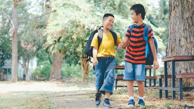 Два мальчика начальной школы со школьными сумками за спиной. Premium Фотографии