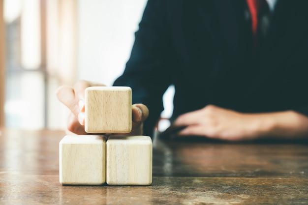 ビジネスマン手手配ウッドブロック事業戦略 Premium写真