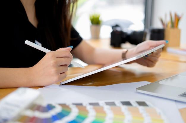Графический дизайнер, работающий на ее столе в офисе творческой студии. Premium Фотографии