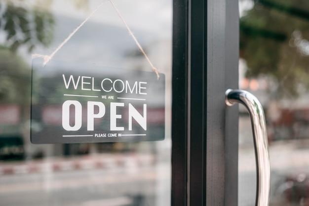 オープンとドアの看板を格納する歓迎のクローズアップ。 Premium写真