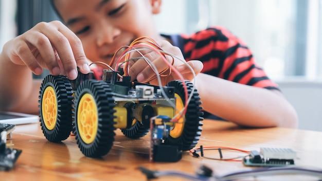 Сконцентрированный мальчик создавая робота на лаборатории. Premium Фотографии