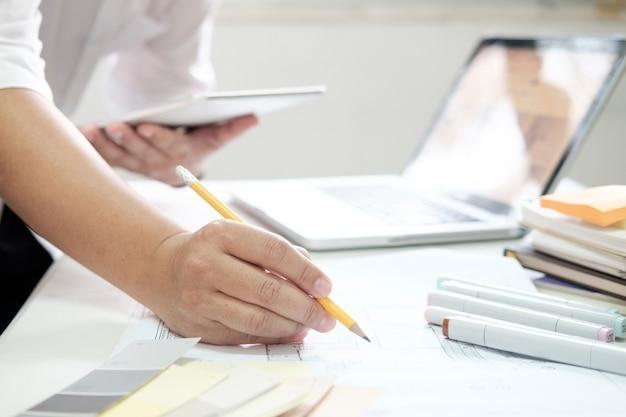 机の上にグラフィックデザインとカラースウォッチとペン。作業工具とアクセサリーを使用した建築図面 無料写真