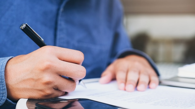 Закройте вверх по бизнесмену подписывая контракт делая сделку. Premium Фотографии