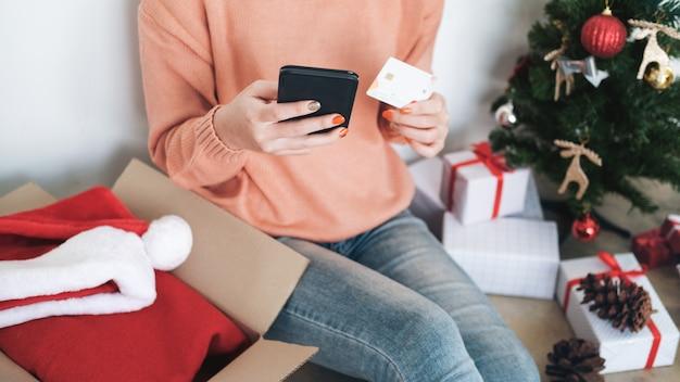 Молодая женщина держа кредитную карточку и делая покупки онлайн. Premium Фотографии