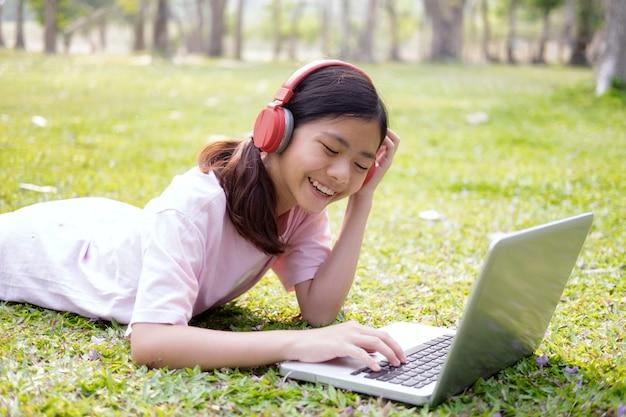 Расслабьтесь и слушайте музыку. девушка с беспроводными наушниками слушает музыку в парке. Бесплатные Фотографии