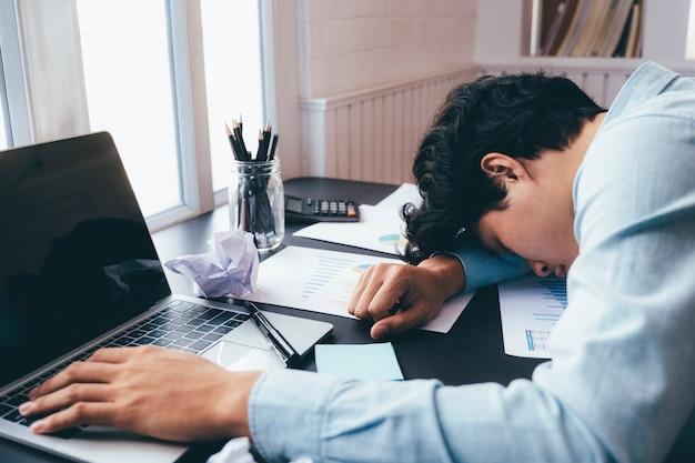 一生懸命働いて、机で寝ている青年実業家。 Premium写真