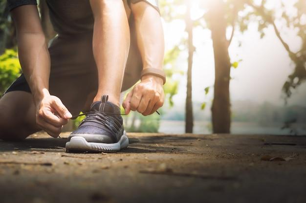 若い男ランナーは靴ひもを結ぶ。 無料写真