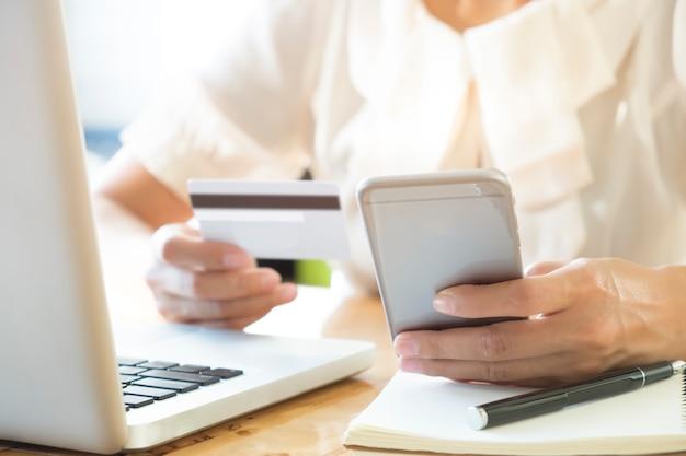 Женщина, держащая мобильный телефон и кредитную карту на ноутбуке для покупок в интернете Бесплатные Фотографии