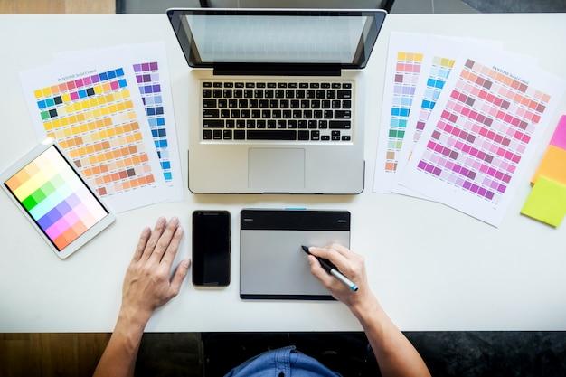 若いグラフィックデザイナーがデスクトップコンピュータで作業し、いくつかの色見本、トップビューを使用していることのトップビュー。 無料写真