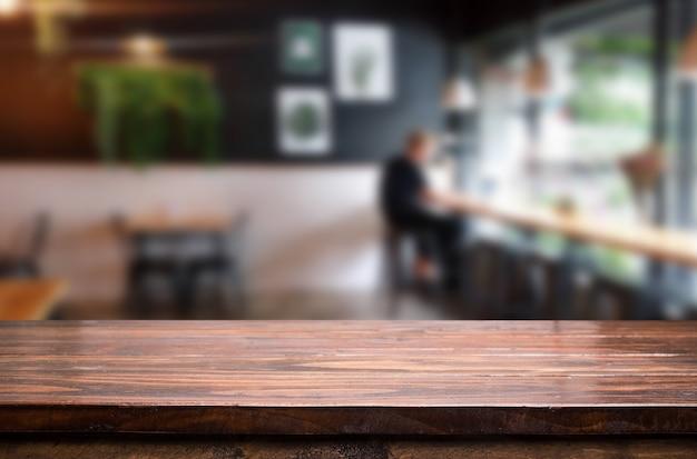 選択されたフォーカス空の茶色の木製テーブルとコーヒーショップやレストランボケの画像を背景にぼかし。あなたのフォトモンタージュまたは製品のディスプレイ用です。 Premium写真