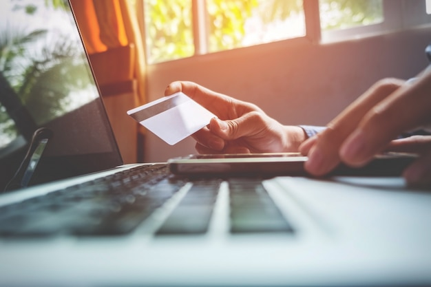 Мужчина держит кредитную карту в руке и вводит код безопасности с помощью смартфона на клавиатуре ноутбука, концепция онлайн-покупок. Бесплатные Фотографии