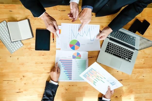 最新のデジタルコンピュータで新しいビジネスプランを作成するビジネスチーム。トップビューショット。 無料写真