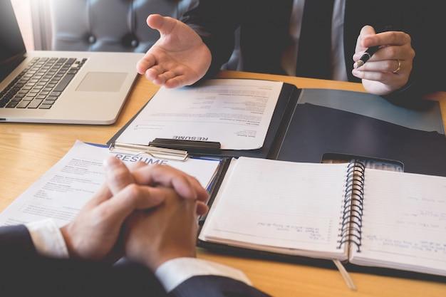 ビジネスマンは彼のプロフィール候補面接の答えについて説明する若い魅力的な男性に耳を傾ける Premium写真