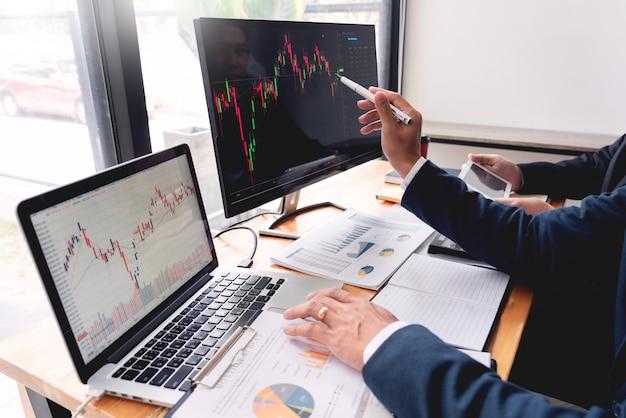 Команда биржевых маклеров обсуждаем с экранами дисплея анализ данных Premium Фотографии