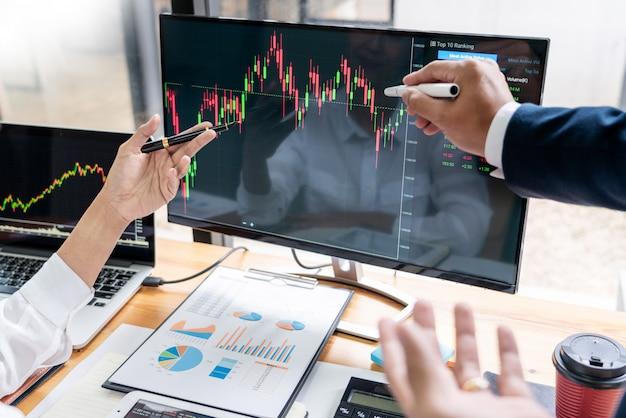 Команда биржевых маклеров обсуждает с экранами Premium Фотографии