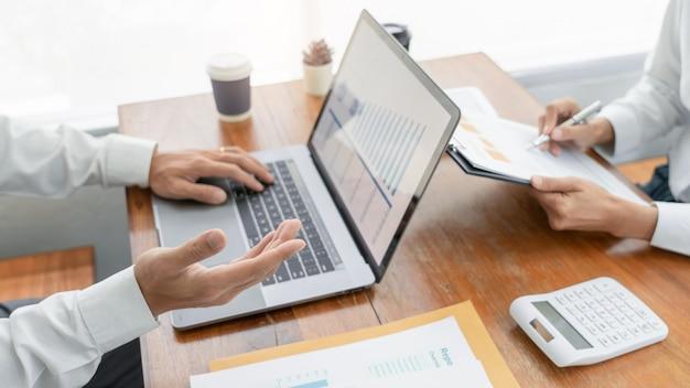 話しているビジネス人々会議と成功したチームワークの概念で財務ドキュメントデータのチャートとグラフを分析する同僚の計画と議論します。 Premium写真