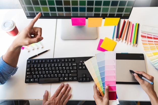 Профессиональный творческий архитектор графического дизайна, выбирающий образцы цветовой палитры для проекта на настольном компьютере Premium Фотографии