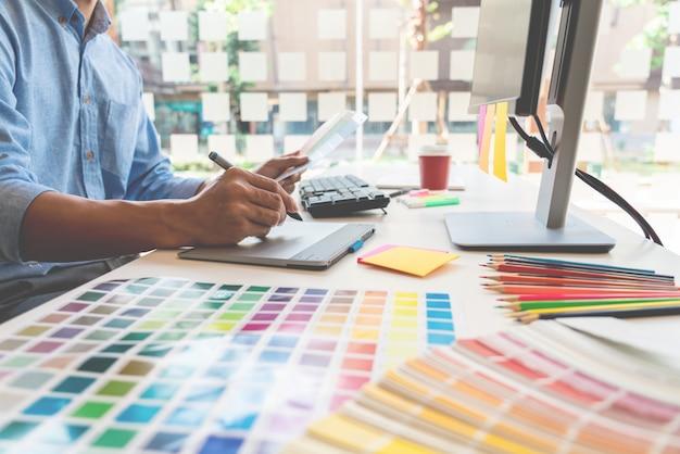 Графический дизайнер работает в офисе Premium Фотографии