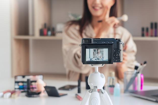 ビデオを録画し、自宅で化粧品を紹介する美容ブロガー Premium写真