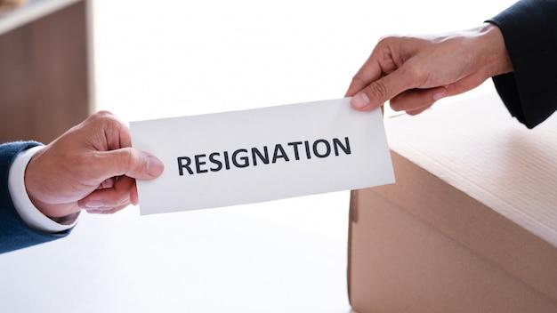 Бизнесмен посылая письмо отставки к исполнительному боссу работодателя на столе для того чтобы уйти в отставку увольняет контракт, размещение работы и концепция вакансий. Premium Фотографии