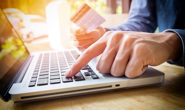 Мужчина держит кредитную карту в руке и вводит код безопасности с помощью клавиатуры ноутбука Бесплатные Фотографии