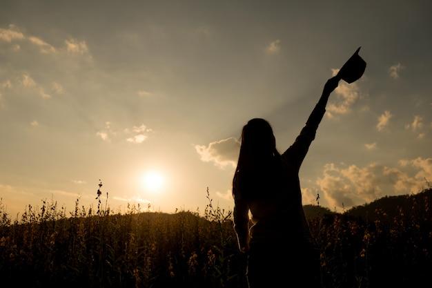 幸福の女性は、太陽の下で花の庭で屋外に滞在 Premium写真