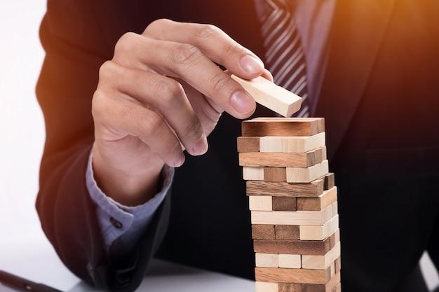 ビジネスコンセプト、タワーに木製のブロックを配置する賭博ビジネスマンで計画、リスクと戦略。 無料写真