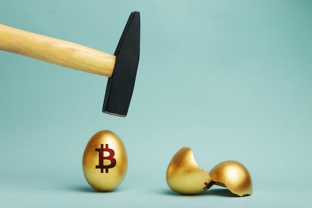 Золотое биткойн, яйцо и молот, зависшие над ним, до удара. разбитое яйцо биткойн. крах биткойнов, концепция потери денег. Premium Фотографии