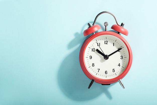 Красный будильник с тенью, лежа на синем. вид сверху. Premium Фотографии