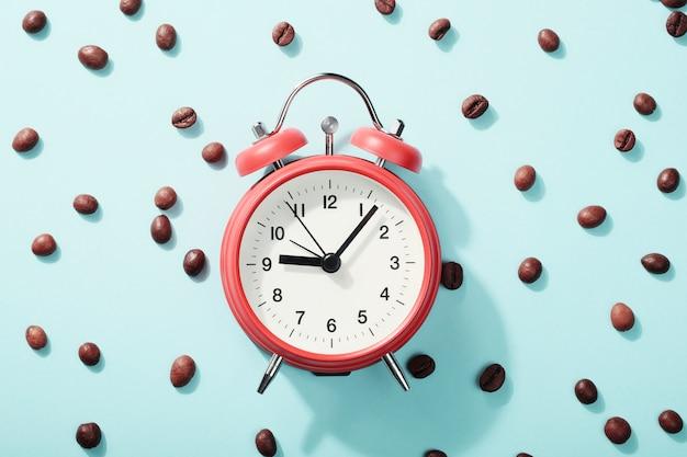 Красный будильник и жареные кофейные зерна. концепция утреннего пробуждения, начало рабочего дня Premium Фотографии