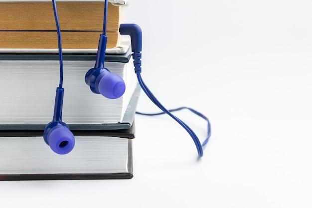 本と白い酷似のヘッドフォン。オーディオブックのコンセプト Premium写真