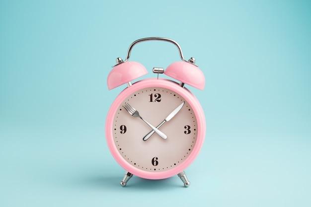 目覚まし時計。時計の針の代わりにフォークとナイフ。断続的な絶食、昼食、食事、減量の概念 Premium写真