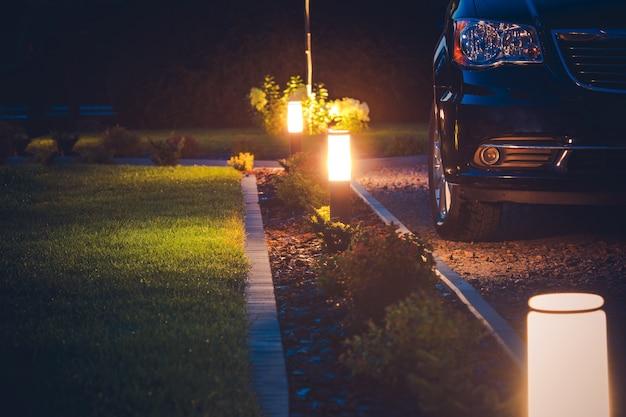 家の私道のイルミネーション。エレガントな前庭の照明。 Premium写真