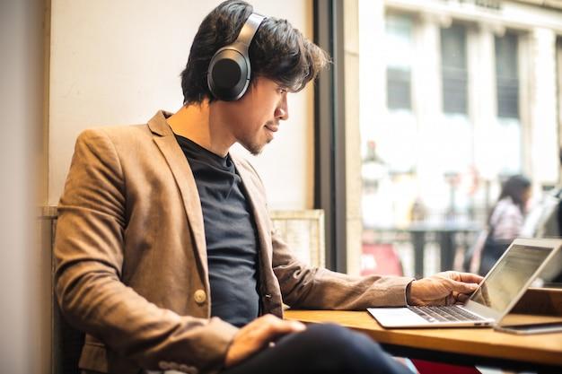 彼のラップトップで働いて、何かを聞いている男 Premium写真