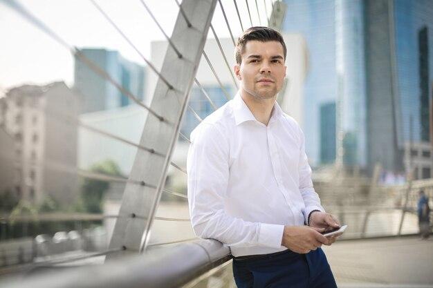 Красивый бизнесмен ждет что-то на улице Premium Фотографии