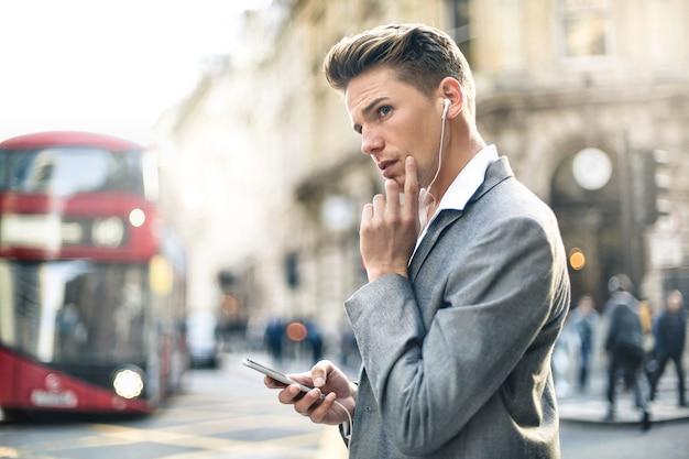 通りを歩きながら電話で呼び出しを持つハンサムなビジネスマン Premium写真