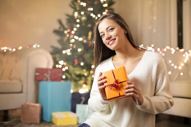 クリスマスプレゼントを持って、リビングルームに座っている甘い女の子 Premium写真