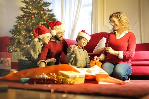 家族一緒に時間を楽しんで、クリスマスプレゼントを開く Premium写真