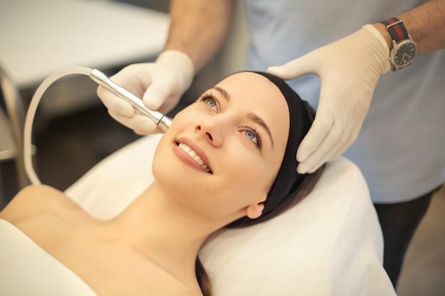 クリニックで皮膚の治療を持っている美しい女性 Premium写真