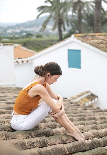 彼女の問題を考えて、屋根の上に座っている悲しい女性 Premium写真