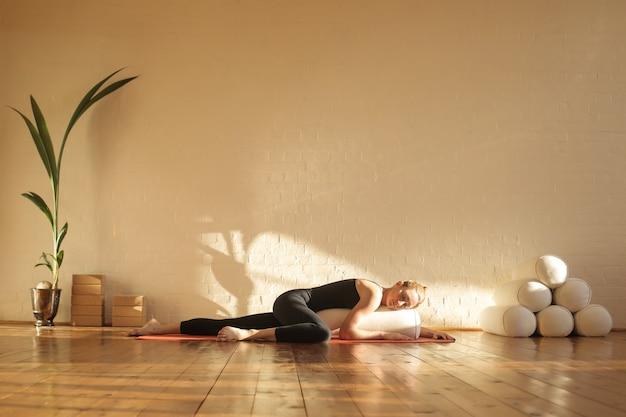 美しいスタジオでリストラティブヨガの練習の女性 Premium写真