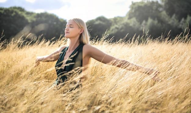 Красивая женщина, ходить в пшеничном поле и дышать глубоко Premium Фотографии