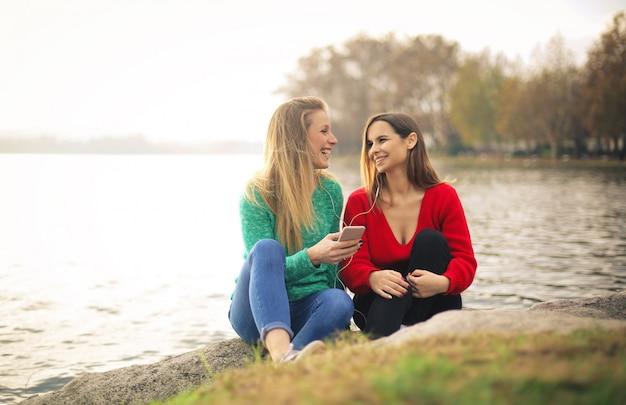 川沿いに座って、イヤホンで音楽を聴く友人 Premium写真