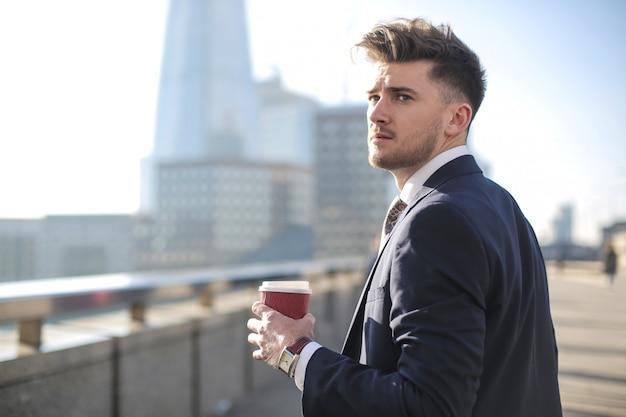 ロンドンの橋の上を歩いてハンサムな実業家 Premium写真