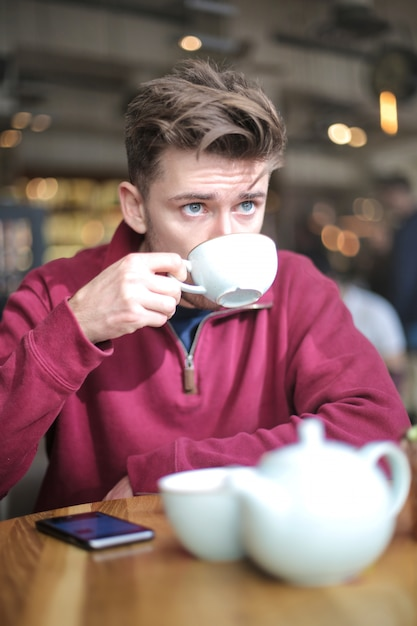 コーヒーショップに座って、お茶を飲む男 Premium写真