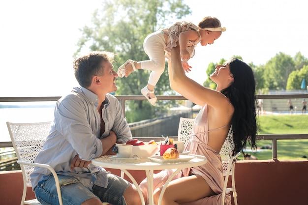 テラスに座って、朝食を持っている素敵な家族 Premium写真