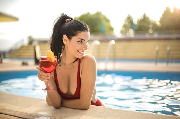 スイミングプールで冷やしながらカクテルを飲む美しい女性 Premium写真